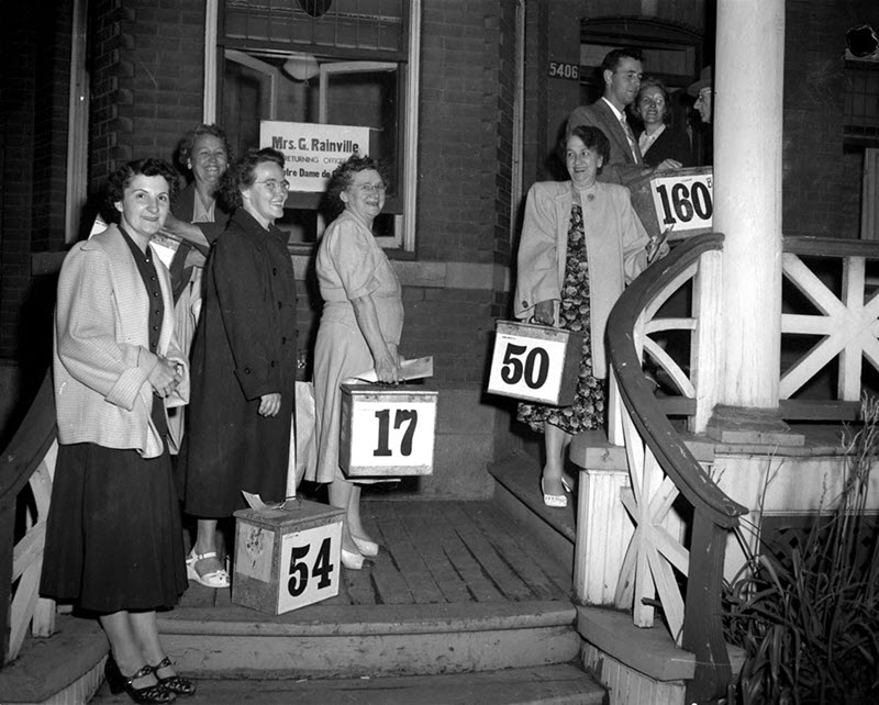 Black and white photo of a group, mostly women, waiting with metal ballot boxes on the steps of an election office