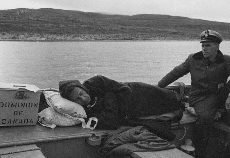 Black and white photo of an election worker lying on a bench on a boat with his eyes closed and a metal ballot box next to his head