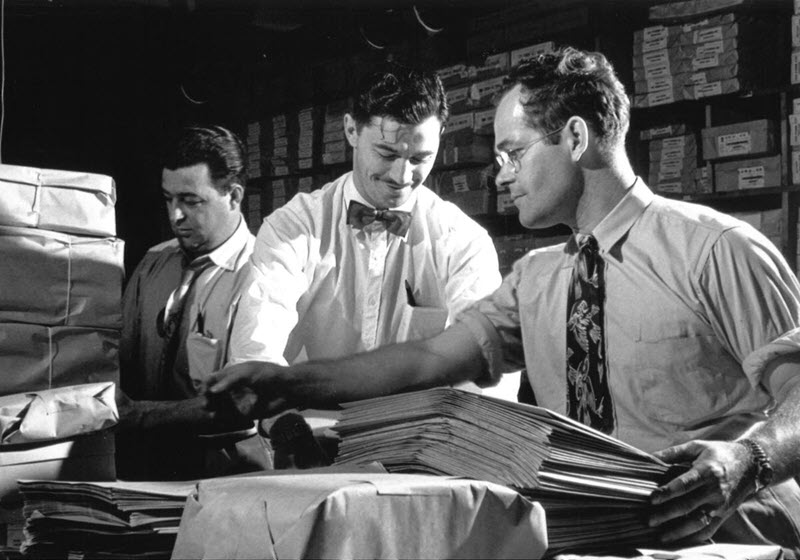 Black and white photo of three election workers organizing packages and documents on a table in a supply room