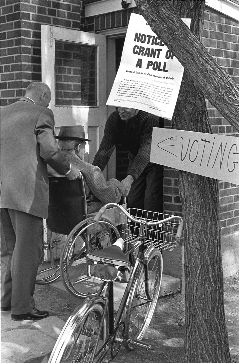 Black and white photo of two men lifting a man in a wheelchair over the threshold of a polling station