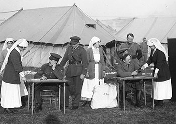 A black and white photograph from 1917: A Canadian military nurse hands a man seated at a polling station table a document related to voting