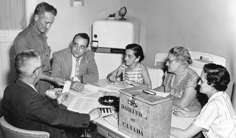 Black and white image of three men and three women sitting around a kitchen table piled with documents, an ash tray and metal ballot box.