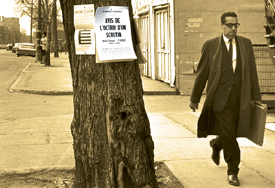 A man wearing a suit and a long coat walks by a tree that has several documents pinned to it, one of which reads 'Notice of Election'.