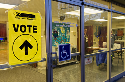 A yellow Elections Canada sign and a blue wheelchair access sign hang on a pair of glass of doors that look into a space being used as a polling station.