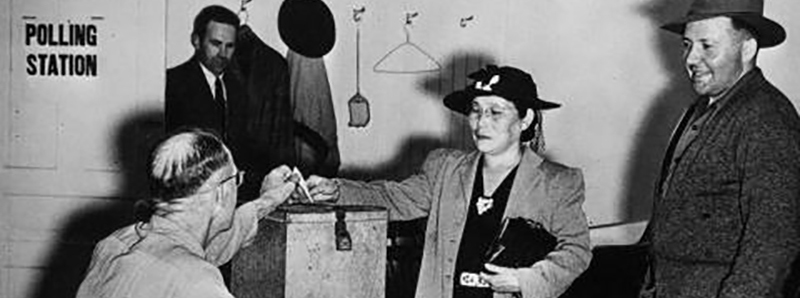 Black and white photo of a Japanese woman wearing a hat and long coat putting a ballot into a metal ballot box.