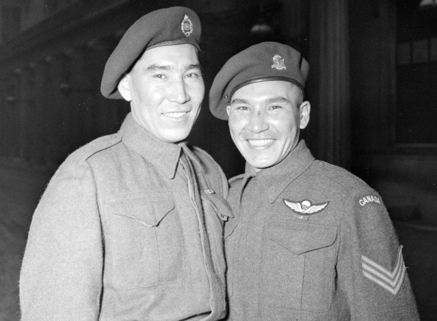 Black and white photo of two young First Nations men wearing military uniforms standing next to each other and smiling
