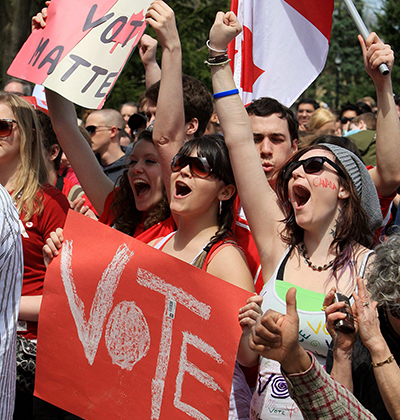 A crowd of young people outside cheer and pump their hands in the air. A young man waves a Canadian flag while a woman in front of him carries a handmade sign with the word 'vote' on it
