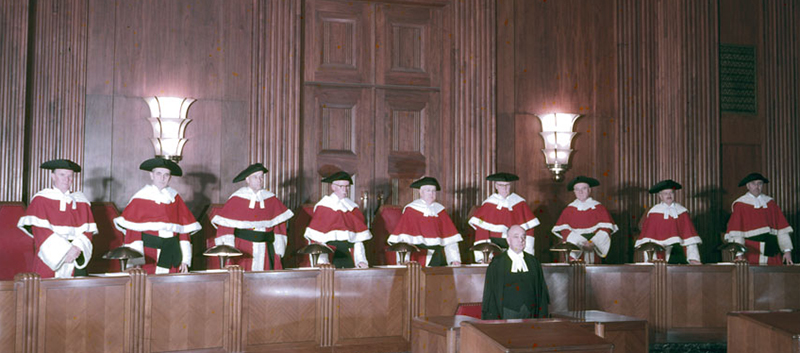 Nine men wearing scarlet Supreme Court of Canada robes trimmed with white fur stand at a long wooden podium