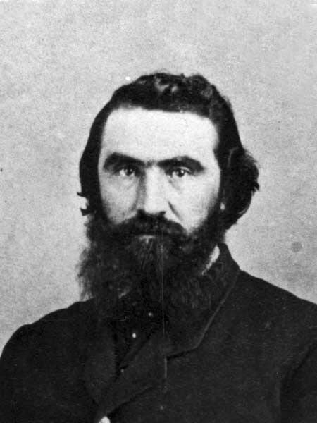 Black-and-white photo of a bearded man in a dark jacket.
