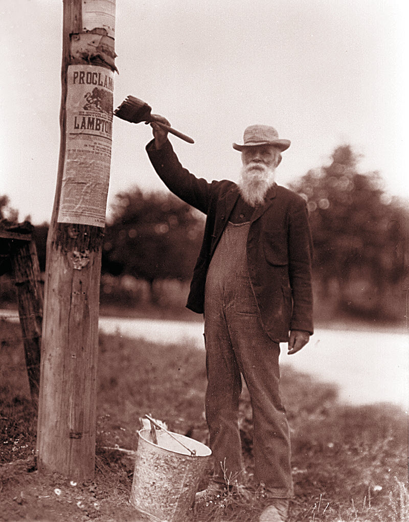 Photograph of an older man pasting an election proclamation poster on a pole using a brush and a bucket of paste.