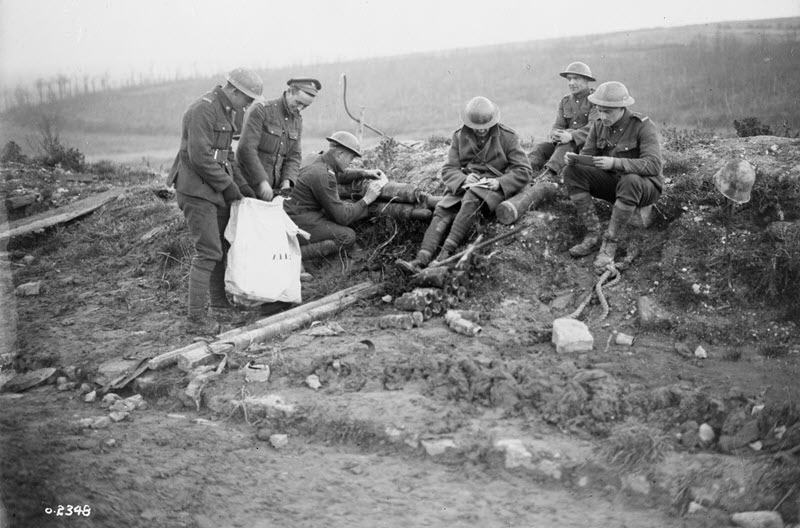 Black and white photograph of six soldiers in First World War uniforms sitting on a mound of earth as they mark election ballots.