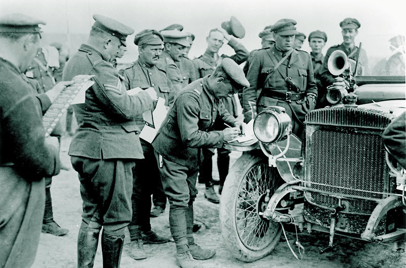 Black and white photo of a dozen soldiers in First World War uniforms holding and marking ballots as they crowd around an antique car.