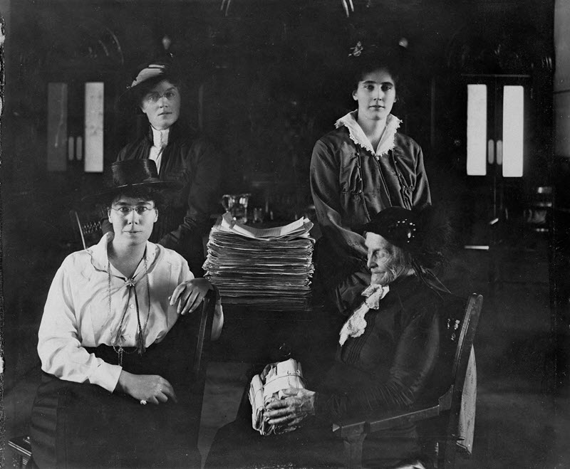 Black and white photograph of four women gathered around a table on which there is a large pile of paper.