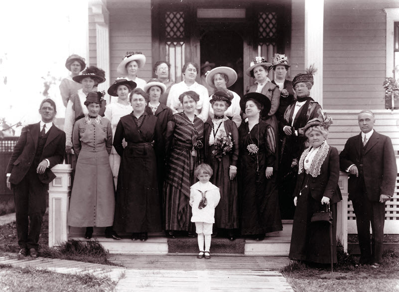 Black and white photo of a group of mostly women in long dresses and hats standing on the porch of a home.