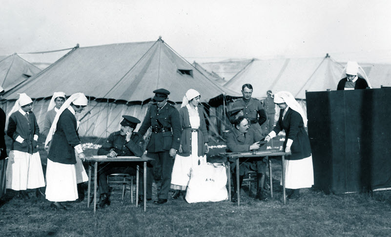 A black and white photograph from 1917 showing women in nurses' uniforms gathered around tables at which soldiers are seated. One of the nurses hands a document to one of the soldiers.